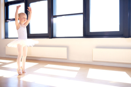 Little girl training to be a ballerina standing in a graceful arms raised position in her white tutu and pink satin ballet shoes in a bright sunlit ballet studio 免版税图像
