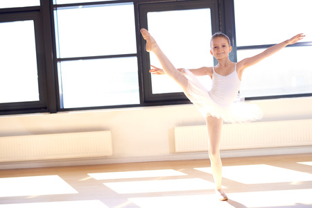Agile pretty young ballerina practicing her positions in a graceful pose in front of bright windows at a ballet school, with copyspace