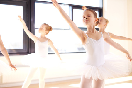 Graceful young ballerinas practising a choreographed ballet during a class at a dance studio, close up against a bright window