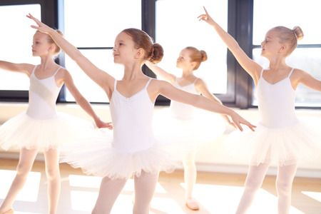 Choreographed dance by a group of graceful pretty young ballerinas practicing during class at a classical ballet school