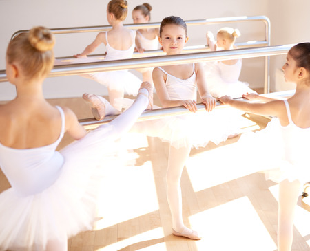 dance bar: Group of pretty young girls in white tutus in a class at the ballet school training at the bar practicing their positions, focus to a ballerina in the centre