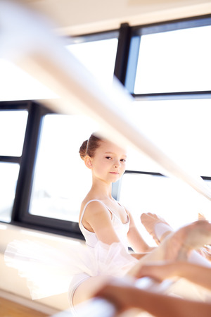 barre: Pretty Ballet Girl Stretching her Leg Using a Bar with her Classmates During Their Ballet Class at the Studio.