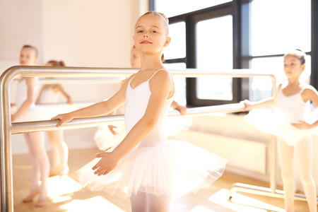 ballet bar: Pretty graceful young ballerina working out at the bar during a ballet class in a bright sunny studio giving the camera a friendly smile