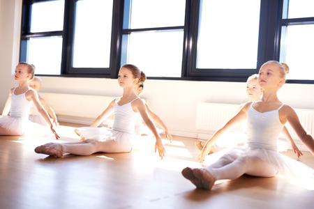 kids class: Group of cute graceful little ballerinas in class sitting on the wooden floor of the studio practising a pose with outstretched arms in front of bright windows Stock Photo