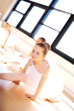 suppleness: Cute Little Ballerina in White Tutu, Splitting her Legs on the Floor While Looking at the Camera During the Training at the Studio