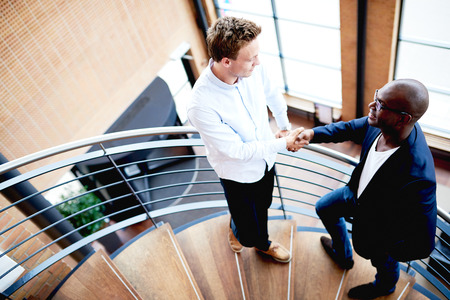 black professional: Two men in modern office building standing on staircase shaking hands and smiling Stock Photo