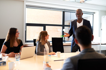 black woman white man: Black male executive standing and leading a work meeting in conference room.