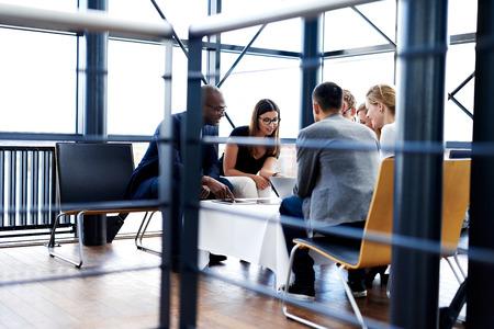 Groupe des cadres assis et travaillent ensemble en utilisant des comprimés et ordinateur portable