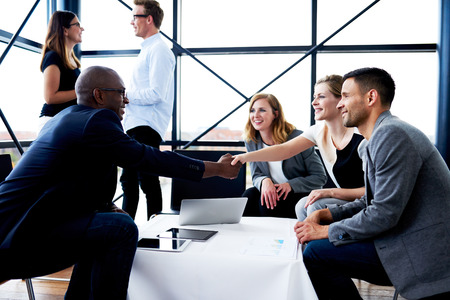 welcome people: Black male executive sitting and shaking hands with white female colleague