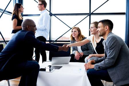 Negro ejecutivo masculino sentado y agitando las manos con su colega mujer blanca Foto de archivo