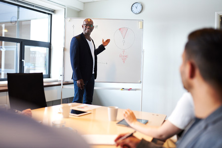Black male executive smiling leading a meeting and pointing to a pie chart on whiteboard