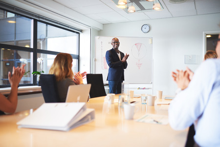 Black male executive standing at head of table in conference room smiling leading meeting