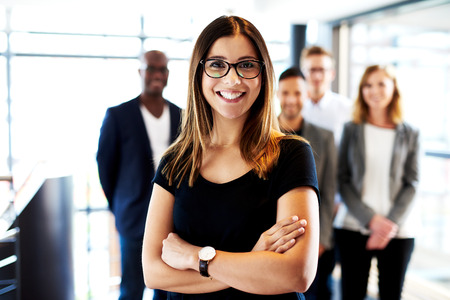 Young white female executive standing in front of colleagues with arms crossed and smiling Stockfoto