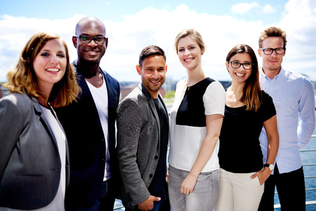 female executive: Group of executives smiling and posing outside for picture.