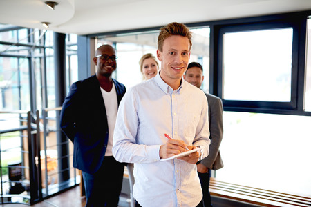 facing on camera: Group of young executives standing in modern work space smiling and facing camera Stock Photo