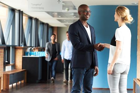 dando la mano: Hombre negro y mujer blanca sonriendo y agitando las manos en edificio de oficinas Foto de archivo