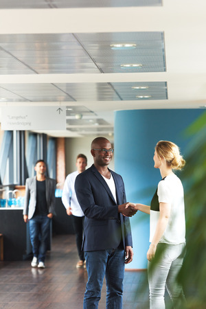 introduction: Black man and white woman shaking hands in office with colleagues walking in background