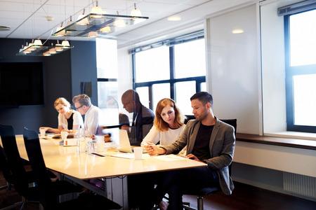 ejecutivo en oficina: Grupo de ejecutivos jóvenes que trabajan y que se sientan a la mesa en la sala de conferencias