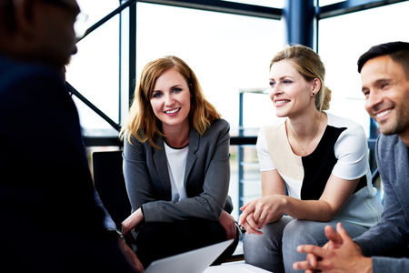 leaning forward: Female white executive smiling at camera leaning forward against knees sitting next to colleagues