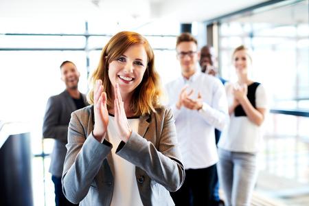 aplaudiendo: Joven mujer de pie ejecutivo blanco delante de sus colegas aplaudiendo y sonriendo Foto de archivo