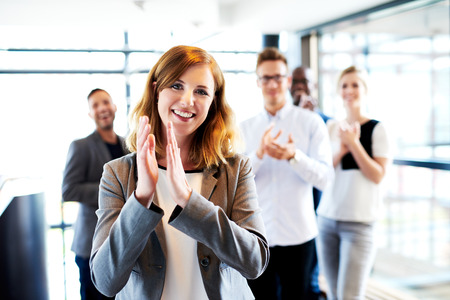 people clapping: Young white female executive standing in front of colleagues clapping and smiling