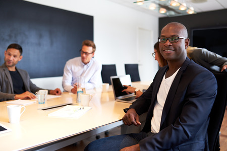 reunion de trabajo: Ejecutivo joven hombre negro sonriente y frente a la cámara durante la reunión de trabajo