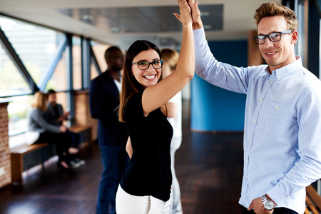 Female and male colleagues high fiving and smiling at camera Stock Photo