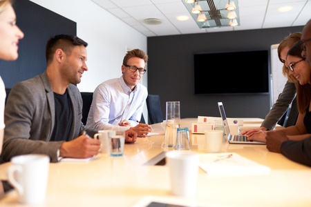 young executive: White male executive smiling at camera during a meeting with colleagues