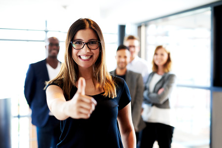 young executive: Young white female executive standing in front of colleagues making thumbs up sign. Stock Photo