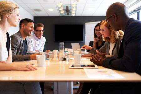 profesionistas: Grupo de jóvenes ejecutivos que tienen una reunión en una sala de conferencias