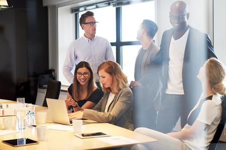 socializando: Grupo de jóvenes ejecutivos de socialización en la sala de conferencias de la oficina