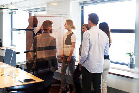 executive: Group of executives standing in conference room gathered around white board