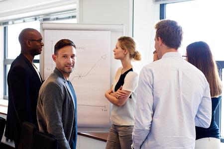 ejecutivo en oficina: Blanca masculina ejecutivo sonriendo a la c�mara durante la presentaci�n del trabajo Foto de archivo
