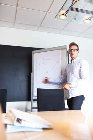 young executive: Young white male executive pointing to a chart on a whiteboard leading a meeting Stock Photo