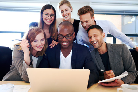 Group of executives smiling and gathered together looking at laptop