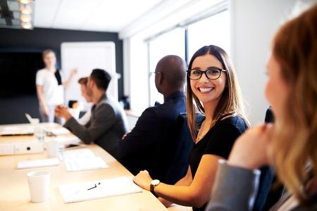 Mujer blanca sonriendo a la cámara durante la presentación del trabajo en la sala de conferencias de la oficina ejecutiva Foto de archivo - 41683504