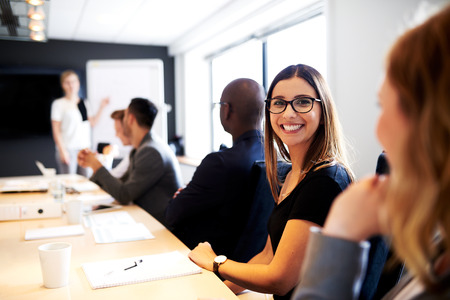 ejecutivo en oficina: Mujer blanca sonriendo a la c�mara durante la presentaci�n del trabajo en la sala de conferencias de la oficina ejecutiva