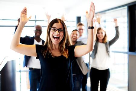 Jonge witte vrouwelijke executive staande voor collega's met hun armen omhoog.