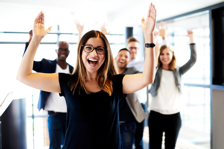 woman arms up: Young white female executive standing in front of colleagues with their arms raised up.