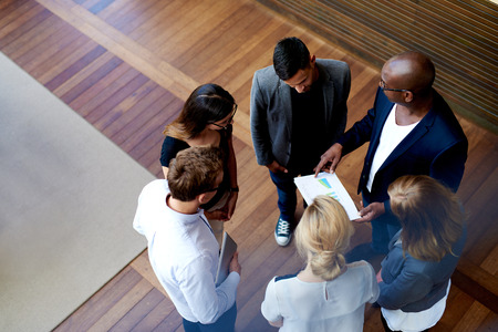 View looking down at colleagues standing in a circle looking at charts on paperwork