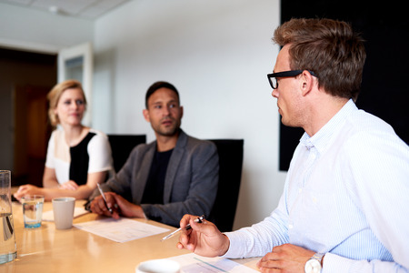 eachother: Young executives facing eachother during a meeting in conference room Stock Photo
