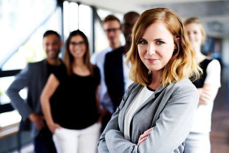 female executive: Young white female executive with arms crossed standing in front of colleagues grinning at camera Stock Photo