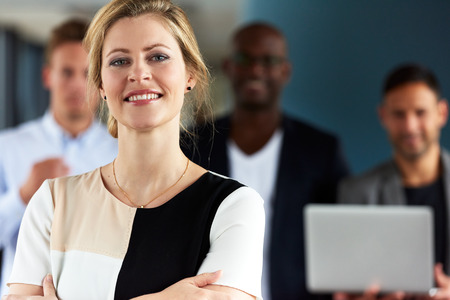 facing on camera: White female executive facing camera with arms crossed and colleagues in background Stock Photo