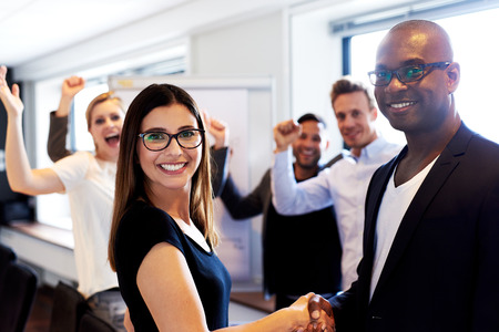 White female colleague and black male colleague shaking hands in front of coworkers flexing arms Foto de archivo