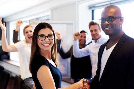 socializando: Compañera de trabajo en blanco y negro colega masculino agitando las manos delante de compañeros de trabajo que dobla los brazos Foto de archivo