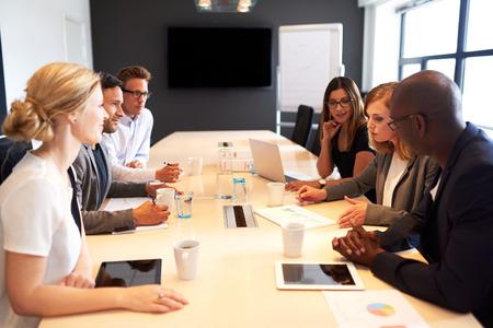 会議室で仕事上の会議を保持している若手経営者のグループ