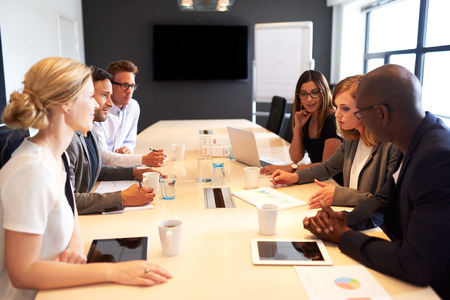 reunion de trabajo: Grupo de ejecutivos jóvenes que sostienen una reunión de trabajo en una sala de conferencias