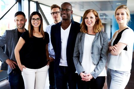 Grupo de ejecutivos jóvenes de pie, sonriendo a la cámara y posando para la foto Foto de archivo - 41683485
