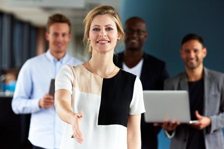 Junge weiße weibliche Führungskraft mit der Hand ausgestreckt, die Kamera und den Kollegen im Hintergrund Standard-Bild