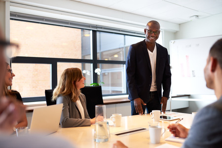 men standing: Black male executive standing and leading a work meeting in conference room Stock Photo